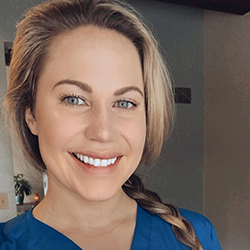 close up of woman in blue scrubs smiling
