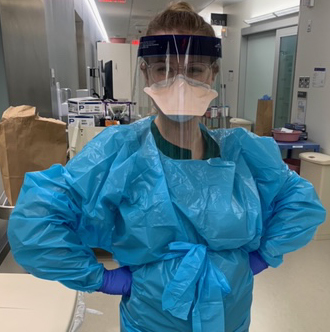 woman in full personal protective equipment standing in hospitcal hallway
