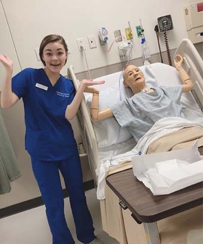 Alpha Tau Delta member in Sim Lab with Mannequin