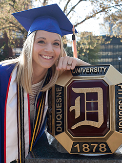 photo of smiling woman in blue graduation gown and hat leaning on Duquesne University Red Ring statue
