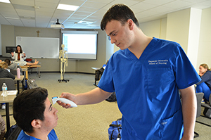 male nursing student using a touch free thermometer on another male student's forehead