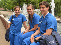 Photo of 3 students in scrubs sitting by a fountain