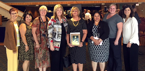 Photo of a group of faculty with Lynn Simko and her 25 years at Duquesne award