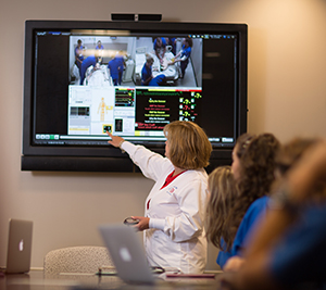 Photo of faculty member reviewing video of a simulation with students