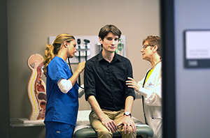 Photo of a student assessing a standardized patient in an exam room