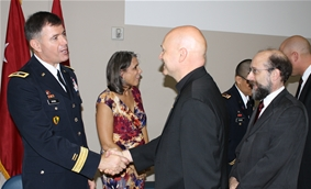 Fr. John Sawicki congratulates Dr. Lew Irwin on his appointment as a U.S. Army brigadier general as Dr. Charlie Rubin looks on, 2012