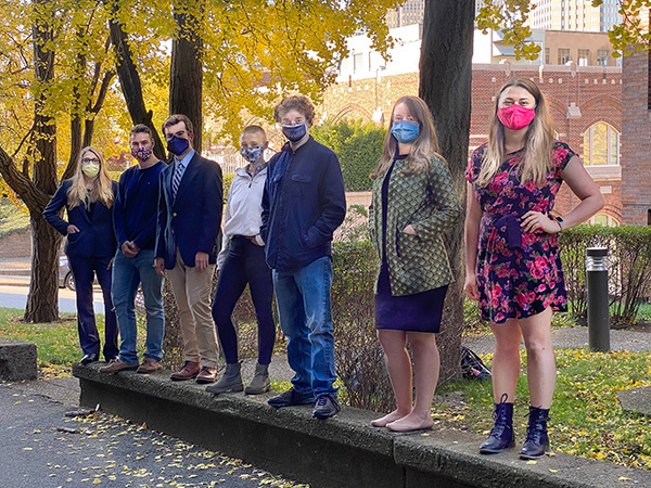 WW Fellows standing outside under fall trees with masks on