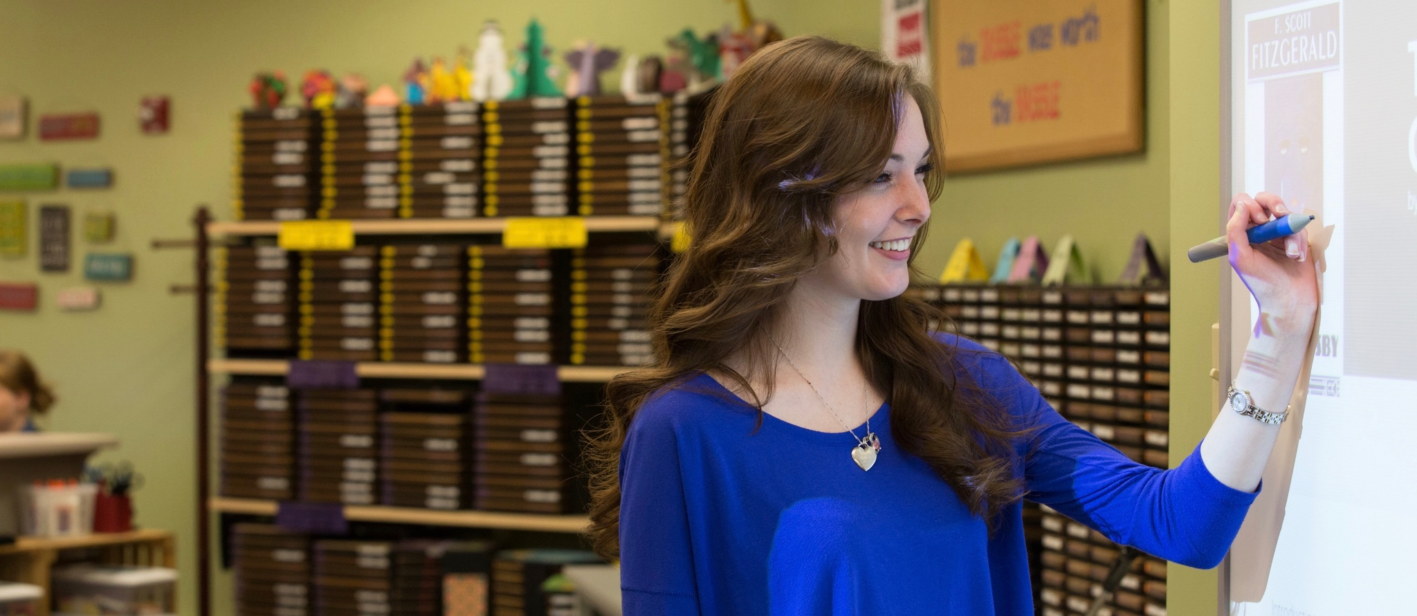 Duquesne student at board teaching in curriculum center