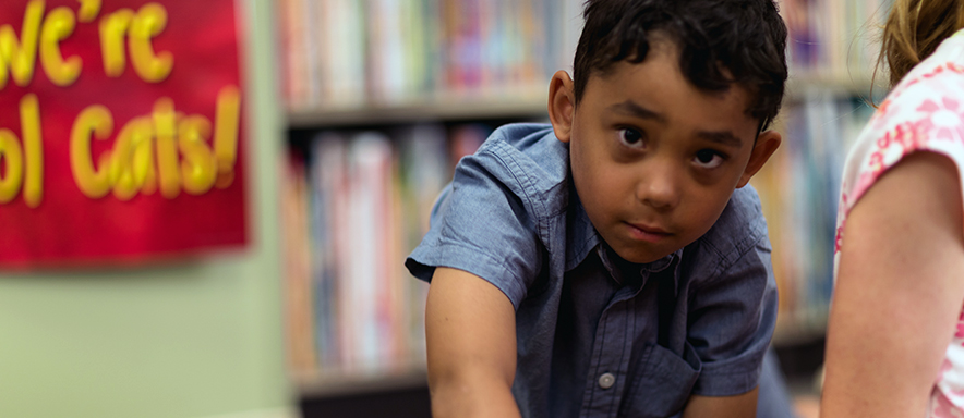 Child looking up against backdrop of books