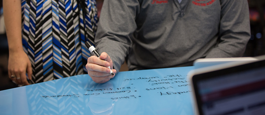 Student and teacher hands writing at smart table