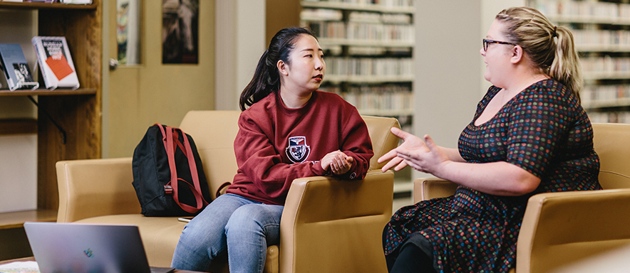 Studen and Instructor speaking in library