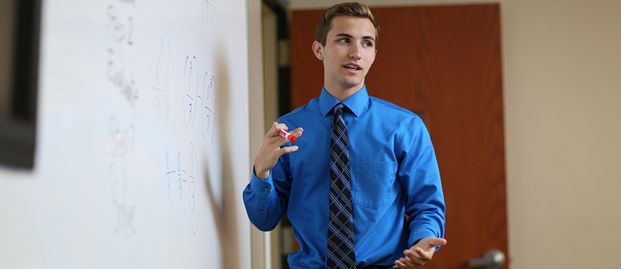 Duquesne student teaching at board
