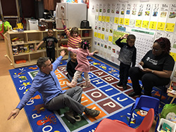 Dr. Meidl engagin in learning game on alphabet mat in childcare center