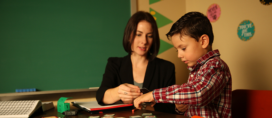 School psychologist working with student with cards