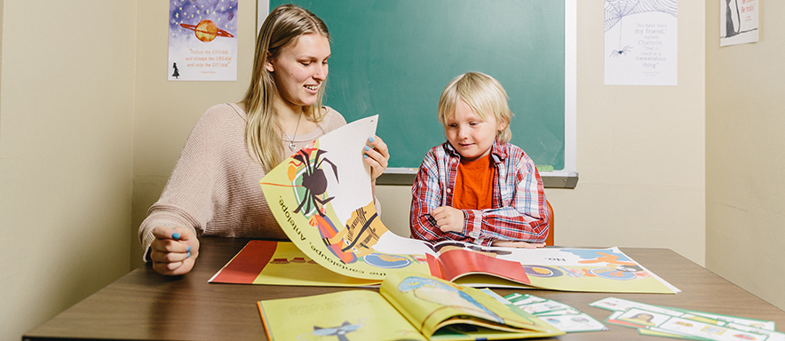 Reading specialist and young student reading book