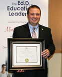 Dr. Mark O'Black holding his UCEA award certificate