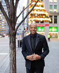Michael J. Warren in downtown Pittsburgh with Chrismas tree on building backdrop