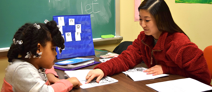 Duquesne student teaching elementary school student at desk